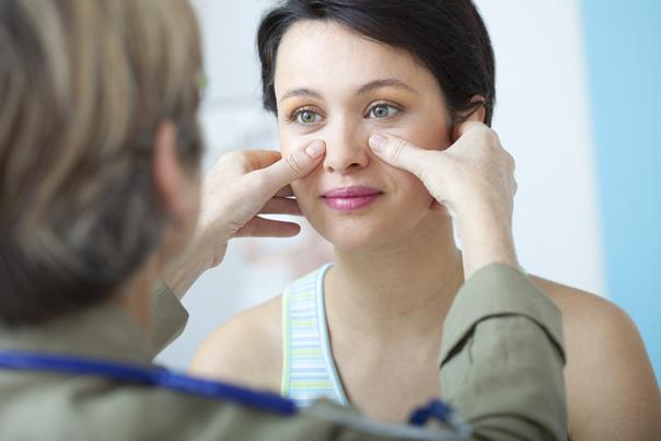 Dr. examina la nariz de una mujer