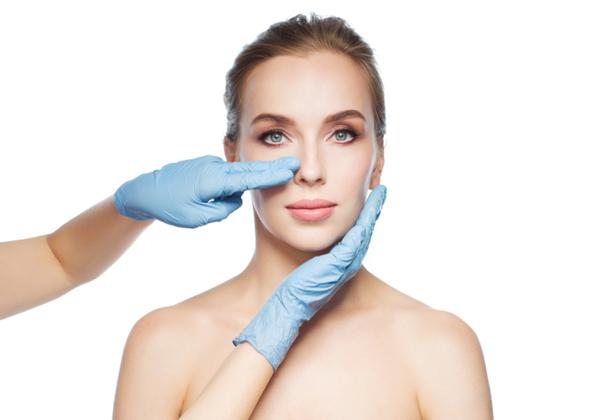 manos de un médica en rostro y nariz de una paciente